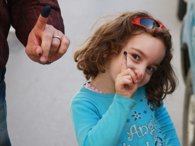 A young Tunisian sports an inked finger like her father's