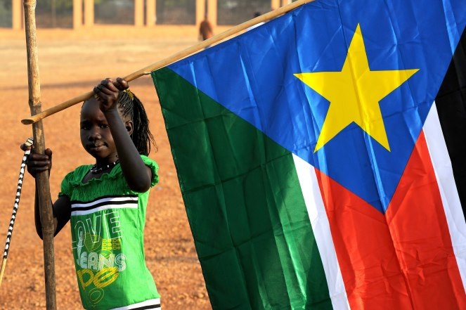 A_young_girl_hangs_the_South_Sudan_flag_(5925619011)